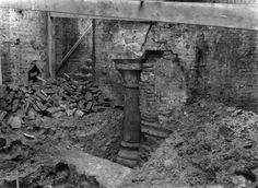 1935-1936. Gezicht in de kelder van de door brand vernielde panden Domplein 16 en Vismarkt 18 (Cabaret La Gaité) met de restanten van het voormalige middeleeuwse paleis Lofen: de zuidelijkste van de twee zuilen, in geheel ontgraven toestand. Daarvóór een ontgraven gedeelte van de stenen walmuur van de 2e Romeinse legerplaats.