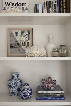 Coastal styled bookcase. Stacked books topped with decorative coral, Ming vase and jar. mercury glass and vintage artwork.
