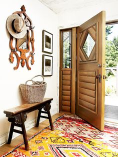 Rustic, country entryway and foyer with bench, wood carved door, and basket