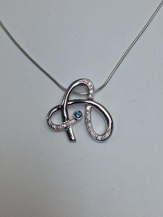 unique hand crafted monogram pendant with teal blue diamond accent from Craft Revival Jewelers
