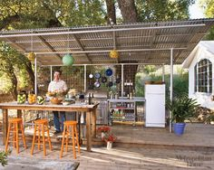 The kitchen is located under a corrugated-metal lean-to outside the main  tent.