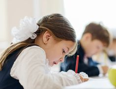 Little girl in class writing with pencil