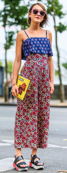 Le look fleuri dans toute la tenue : un pantalon fluide taille haute rouge et un haut bleu crop top à motif avec des lunettes roses, une pochette jaune et des chaussures ouvertes en cuir noir compensées.