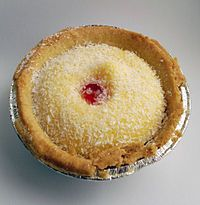 The Manchester tart is a traditional English baked tart, which consists of a shortcrust pastry shell, spread with raspberry jam, covered with a custard filling and topped with flakes of coconut and a Maraschino cherry. One variation of the original recipe includes slices of banana underneath the custard with the jam.