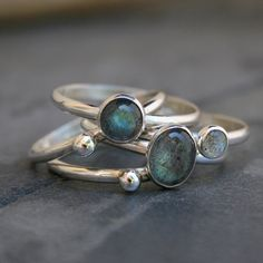Luscious Labradorite Stacking Ring Mix. These semi-transparent gemstones show flashes of different colors depending on the angle in which they are viewed. The ground color of labradorite is a smoky gray, but when light strikes the stone in a particular direction, it displays different