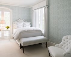 Shared kids' room features walls clad in blue print wallpaper lined with white…
