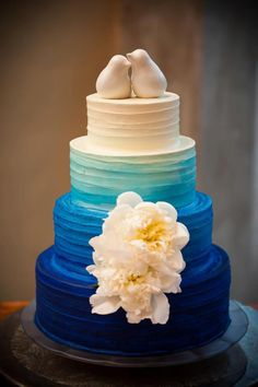 our blue ombre wedding cake with white garden roses; I love the bird cake toppers