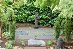 This small Zen garden, with its simple plants, includes a sitting Buddha with both hands in a meditative pose.