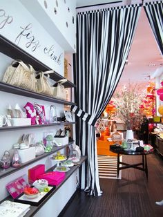 Kate Spade Soho   The black and white wall and stripped curtains add visual interest.  www.giftshopmag.com