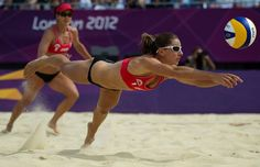 Annie Martin (right), of Canada, dives to bump a ball during a match against Italy in women's beach volleyball during the London 2012 Olympic Games in London, England...