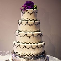 an elegant scrollwork & pearl cake topped with deep purple fresh flower top