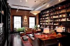 Luxury loft apartment library in Tribeca, New York City; My dream library! I love the dark wood, brick and rust accents. Cozy.