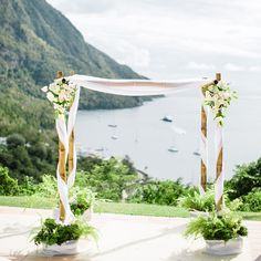 Brides.com: 30 Amazing Ceremony Altars. A bamboo wedding altar with gauzy draped fabric and white flower arrangements, created by Jardin Tropical.
