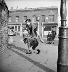 Boys playing leapfrog in the street, London, England, 1953