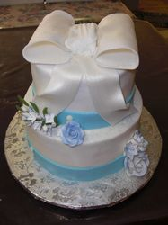 two tiered bc cake with fondant ribbon and bow along with gumpaste flowers