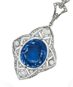 A Sapphire and Diamond Pendant Necklace, circa 1920  The elongated quatrefoil motif set with an oval sapphire weighing approximately 15.25 carats, amid a diamond-set plaque finely millegrained and pierced with floral and foliate details, diamond-set bail, mounted in platinum, and suspending from a silver rope linking chain joined to a platinum and 18k white gold clasp accented by tiny diamonds and simulated sapphires, length 18 3/4 ins