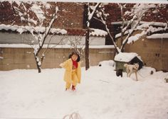 When I was young. On a winter day at my fine art teacher's snowy garden with two dogs.