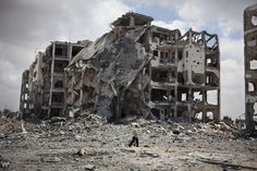 """""""The Annihilation of The Familiar exhibition"""", Qalandiya village, as part of Qalandiya International 2014. A man walks through the remaining structure of a group of buildings in the northern part of Jabalya. The photo was taken on the 4th of August of 2014, during the first hours of a 72 hours cease-fire that was broke a few hours later. Photo: © Eduardo Soteras Jalil."""