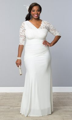 Turn heads on your wedding day in our plus size Elegant Aisle Wedding Gown.  Beautiful lace adorns the top with a delicate mesh one-shoulder overlay that continues throughout the asymmetrical drop waist.  A flowy long skirt lets you move with ease as you walk down the aisle.  Explore more made in the USA bridal dresses at www.kiyonna.com.  #KiyonnaPlusYou