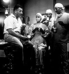 "Stranley Kramer, director, with Olivia De Havilland, Frank Sinatra, and Robert Mitchum on the set of ""Not as a Stranger,"" 1954."