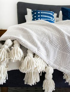Create a high end looking Giant Tassel Throw Blanket by purchasing a fun patterned blanket and adding some chunky yarn tassels!