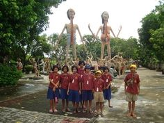 A school trip leads a clasroom of Thai kids to the graphic depictions of Buddhist hell in Saen Suk Temple, Thailand.