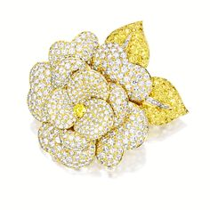 FANCY VIVID YELLOW DIAMOND AND DIAMOND 'CAMELLIA' BROOCH, VAN CLEEF & ARPELS The flower brooch centring on a brilliant-cut fancy vivid yellow diamond weighing 0.26 carat, to petals set with brilliant-cut diamonds, and leaves set with brilliant-cut yellow diamonds, enhanced by a tapered baguette diamond-set stem, the diamonds together weighing approximately 14.50 carats, mounted in 18 karat yellow gold, signed and numbered NY58746.