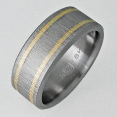 Titanium ring with two flush-set bands of 18k gold with a raw-silk finish. Handcrafted by Chris & Sandy Boothe. $704.00 at TitaniumRingsForever.com