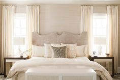 neutral bedroom. beige, white, ivory, and taupe. upholstered headboard. bordered duvet. modern side tables. color block cube tables. nickel curtain rod. bedroom toss pillows.