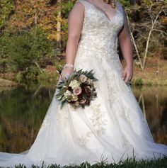 Beautiful ivory and champagne wedding gown with pretty fall bouquet.