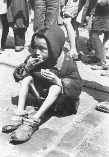Criança emaciada comendo algo nas ruas do Gueto de Varsóvia. Varsóvia, Polônia.  Foto tirada entre 1940 e 1943.