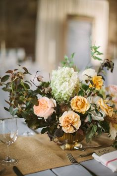 Gold and peach centerpiece consisting of peonies, garden roses, ranunculi, wild clematises, hydrangeas, grasses, vines, and foraged branches   Photo by Cmostr   Floral design by BRRCH