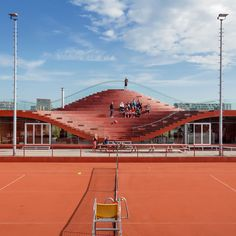 The roof of this bright red tennis clubhouse by Rotterdam firm MVRDV doubles up as an expansive seating area for game spectators.