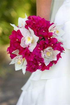 Bright fuchsia bougainvillea bouquet with white cymbidium orchids.