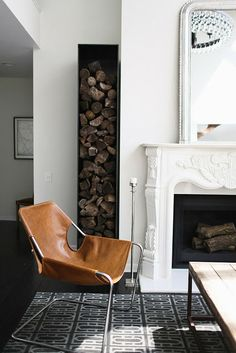 Interior designer Catherine Kwong. In the living room, the dramatic cold-rolled steel log-holder, handcrafted in San Francisco by Ferrous Studios, makes a bold modernist contrast to the custom-designed hand-carved limestone fireplace and a romantic antique silver-leave over-mantel mirror.