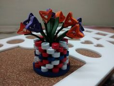 A bouquet with collection of violet and orange flowers with a vase to hold id