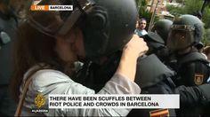 Las cámaras de la cadena catarí Al Jazeera captan la escena de una manifestante besando a un antidisturbio durante las acciones policiales en Barcelona con motivo del referéndum ilegal