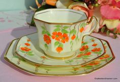 Radfords Art Deco teacup, saucer and tea plate trio. c.1928+  Cream coloured, octagonal shaped vintage bone china. Hand painted orange and green flower pattern and gold gilded rims.  Teacup 8.5cm wide x 7cm tall. 14.5cm Saucer and 17.5cm Tea Plate.  Beautiful Art Deco period china made by Samuel Radford, High St., Fenton, Staffordshire, England. c.1928+  In excellent condition.