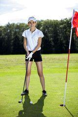 Pretty girl playing golf on grass