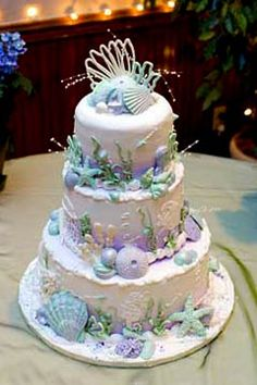 Three tier white wedding cake decorated with purple, blue and green seashells and decorations. Perfect for a beach wedding theme. from www.carlocksbakery.com