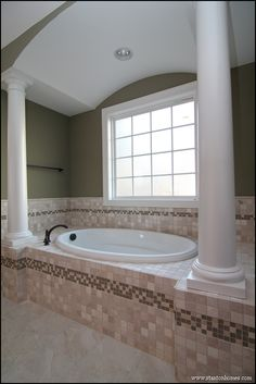 Looking for luxury bath designs? This master bathroom alcove tub has a barrel vault above, white columns, and custom tile surround.