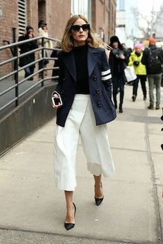 Olivia Palermo in a sophisticated combination of white trousers and navy blazer.