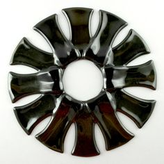 """This glass sculpture would make a charming candle ring or a statement on a wall. Measures 2"""" diameter inside and 8"""" diameter outside. Created from fused bottles. This piece is handmade from recycled g"""