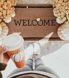 autumn and fall aesthetic | welcome mat, jeans, pumpkin, coffee cup, and flowers
