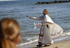 Norfolk, VA: Fr. John Cox of Dormition of the Theotokos Church throws a wooden cross into the Chesapeake Bay from the beach in Ocean View.