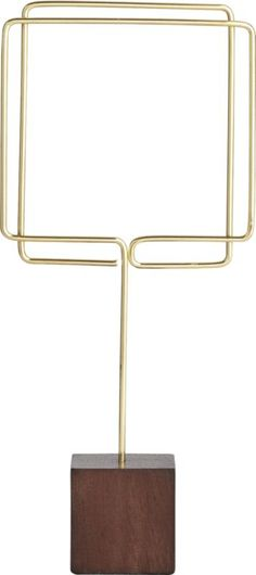 'flash of brass.  Freestanding holder squares up photos in a fluid frame of brass wire that makes is easy to swap in new pics.  Stands solid on a smooth cube of rubberwood. Steel wire with brass finishRubberwood block baseWipe clean with dry clothMade in China.' from the web at 'https://i.pinimg.com/236x/0b/cf/9a/0bcf9a56c1df212e2dcff6535603b3b9--picture-holders-photo-holders.jpg'