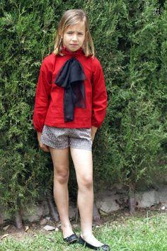 Blusa en algodon-viscosa roja adornada con volante en cuello y lazada en gasa negra.