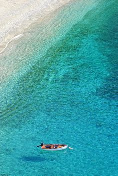 Crystal Clear Photograph.  Small boat moored off the baech in Monterosso al Mare in Cinque Terre, Italy by Paul and Helen Woodford