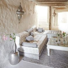 gorgeous grecian feeling cave like living room with thick white plaster walls and built-in sofa with tufted pillow cushions and metal sconces and rough wood ceiling beams. earthy boho natural clean simple cozy and inviting