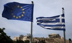 A European Union flag (L) and a Greek national flag flutter in front of the ancient Parthenon temple in Athens.